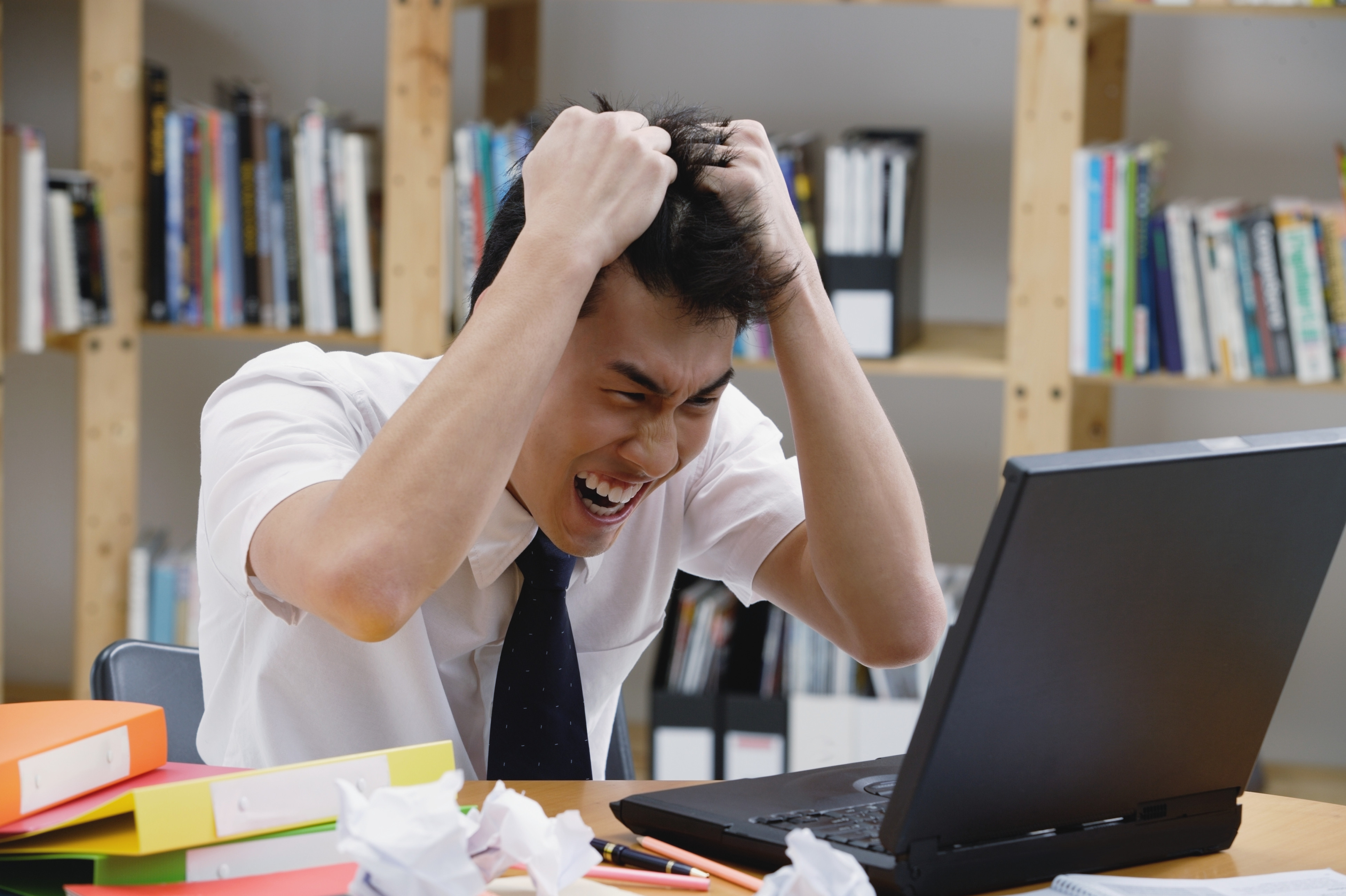 Young man in library, pulling his hair, looking at laptop
