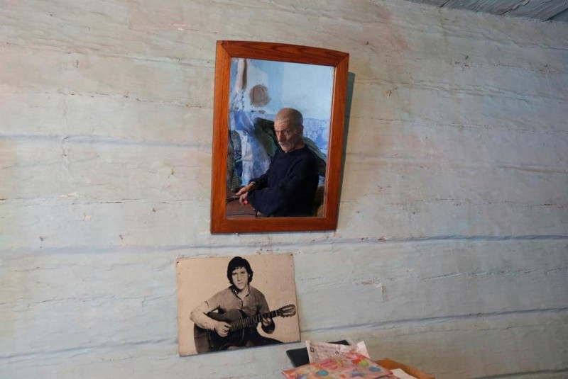 Mikhail Baburin, 66, is reflected in a mirror next to a portrait of Soviet singer, poet and actor Vladimir Vysotsky while he makes a broom at his house in the remote Siberian village of Mikhailovka, Krasnoyarsk region, Russia. He moved in 2000 to Mikhailovka where he was born and has lived there all alone for the last 10 years with only domestic animals. REUTERS/Ilya Naymushin