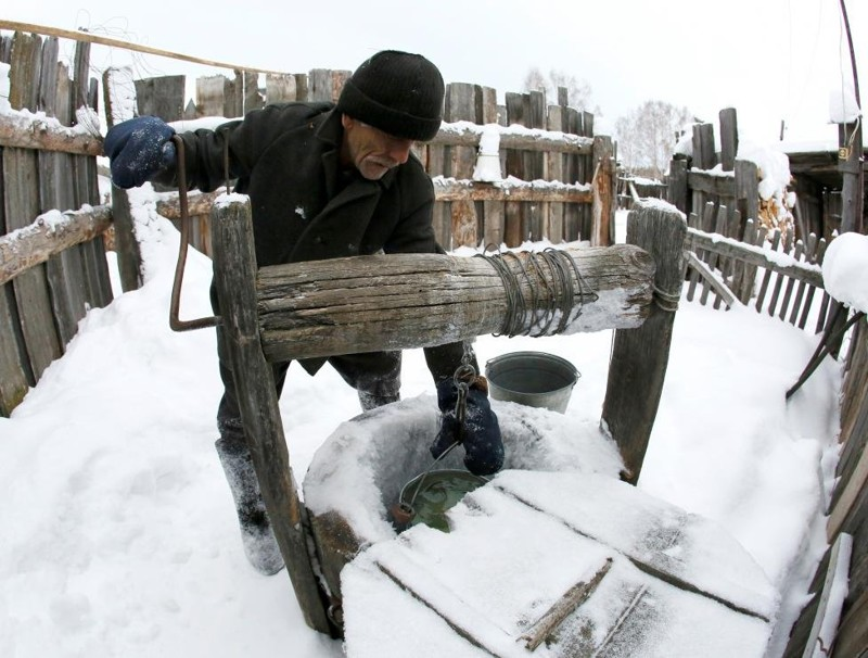 Mikhail Baburin, 66, takes water from a well at a court yard of his house in the remote Siberian village of Mikhailovka, Krasnoyarsk region, Russia. REUTERS/Ilya Naymushin