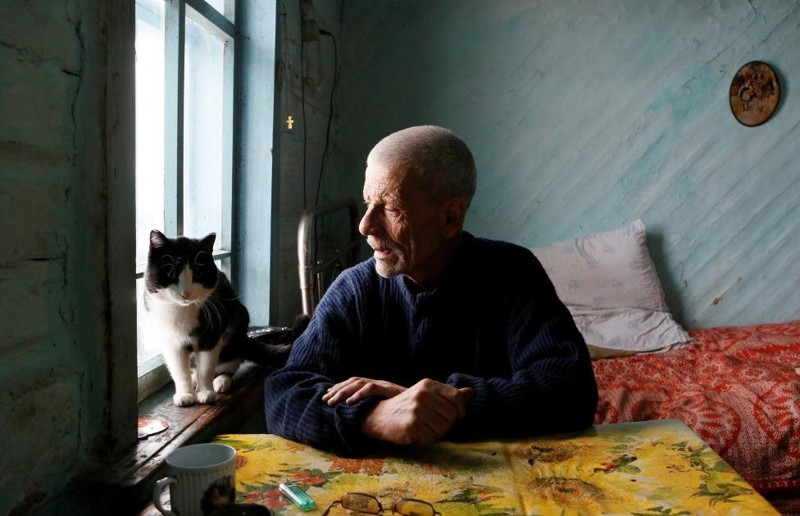 Mikhail Baburin, 66, talks to his cat Marquis at his house in the remote Siberian village of Mikhailovka, Krasnoyarsk region, Russia. Baburin, a former Navy man, barge worker and employee of a military plant in Krasnoyarsk, is the last inhabitant of Mikhailovka, which was founded in the 19th century by migrants from Russia's Mordovia region. REUTERS/Ilya Naymushin