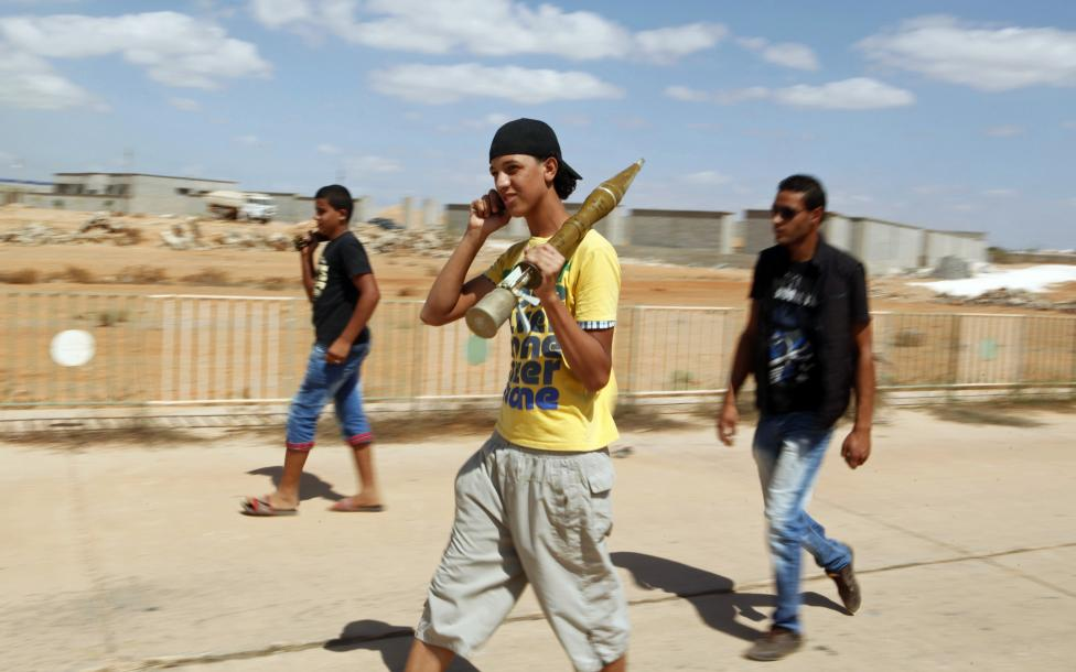 A youth, with a rocket-propelled grenade (RPG) shell, uses his mobile phone as he walks out of the Rafalla al-Sihati brigade base, part of the Libyan army, after it was attacked by demonstrators in Benghazi city September 22, 2012. REUTERS/Asmaa Waguih