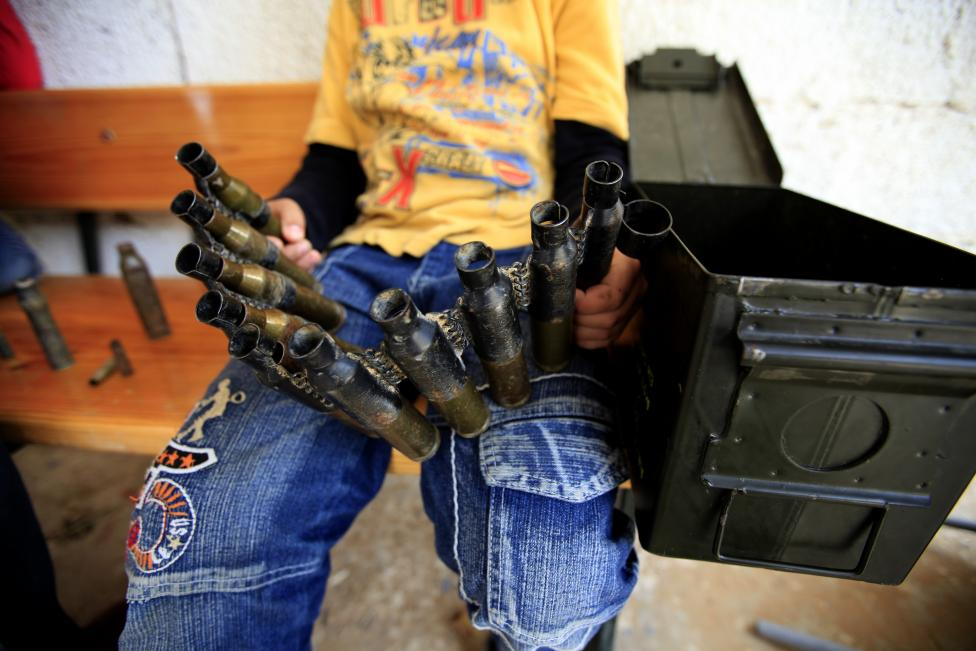 A boy displaced with his family by fighting in Misrata holds empty ammunition shells as he plays war games at a special needs school, in Libya May 25, 2011. REUTERS/Zohra Bensemra