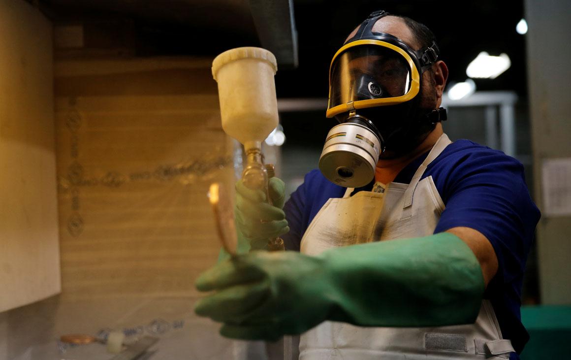 A worker from the Casa da Moeda do Brasil (Brazilian Mint) varnishes a Rio 2016 Olympic medal in Rio de Janeiro, Brazil, June 28, 2016.  REUTERS/Sergio Moraes