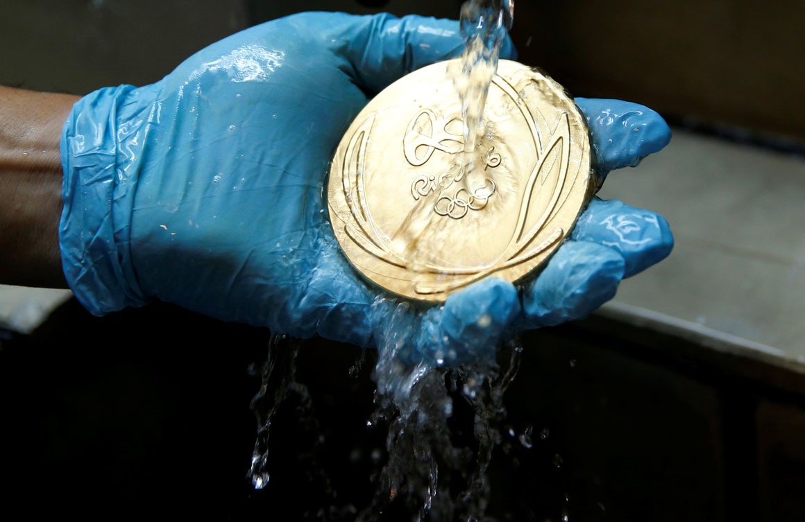 A worker from the Casa da Moeda do Brasil (Brazilian Mint) cleans a Rio 2016 Olympic medal in Rio de Janeiro, Brazil, June 28, 2016.  REUTERS/Sergio Moraes