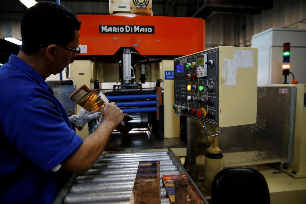 A worker from the Casa da Moeda do Brasil (Brazilian Mint) checks plates to prepare the Rio 2016 Olympic and Paralympic medals in Rio de Janeiro, Brazil, June 28, 2016.  REUTERS/Sergio Moraes