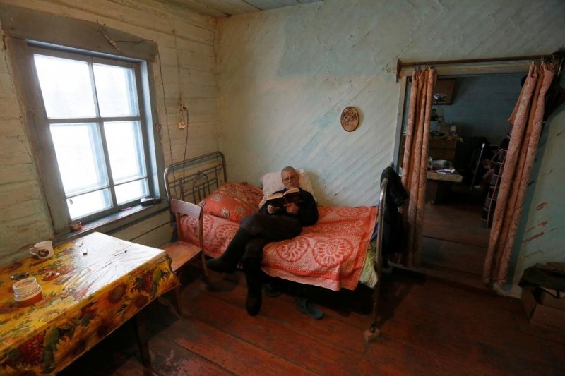 Mikhail Baburin, 66, reads a book at his house in the remote Siberian village of Mikhailovka, Krasnoyarsk region, Russia. REUTERS/Ilya Naymushin