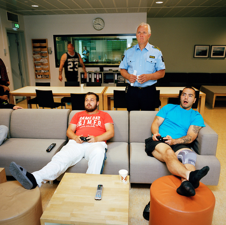 Halden Prison, Norway, June 2014: Inmates playing TV games on a large TV screen in the common area in C8, a special unit for addiction recovery. Governor Are Høidal standing. -- No commercial use -- Photo: Knut Egil Wang/Moment/INSTITUTE