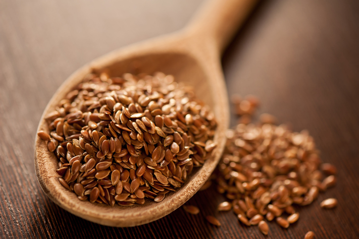 Brown flax seeds heap on wooden spoon closeup, healthy raw seeds portion in day light, horizontal orientation, nobody.