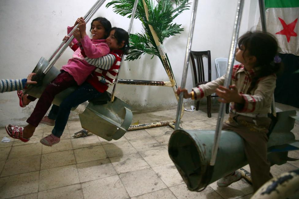 Children ride on makeshift swings made from remnants of rockets at a basement in the Duma neighbourhood in Damascus, on the second day of Eid al-Adha October 16, 2013. REUTERS/Bassam Khabieh