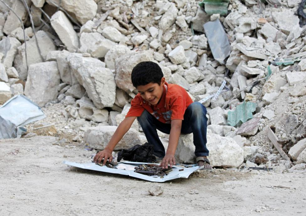Ahmad, a Syrian boy, shows his collection of shrapnel and empty bullets in front of a destroyed house in Aleppo's Tariq al-Bab district September 12, 2012. Ahmad is collecting a piece from each shell that falls on his district and keeps them as souvenirs. REUTERS/Zain Karam