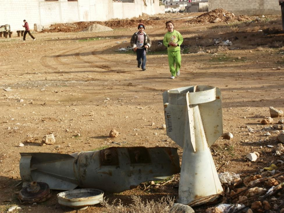 Children play near the remnants of a bomb shell in the ground, which activists said were fired by a Syrian Air Force fighter jet loyal to Syria's President Bashar al-Assad, in Daraya near Damascus December 23, 2012. REUTERS/Fadi Al-Derani/Shaam News Network/Handout