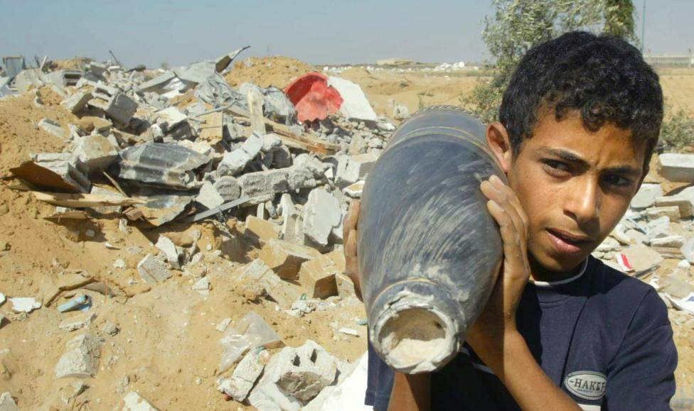 A Palestinian boy holds an Israeli artillery shell as he walks next to the remains of a house after it was demolished by Israeli troops before they pulled out from Rafah camp in the southern Gaza strip August 8, 2006. REUTERS/Ibraheem Abu Mustafa