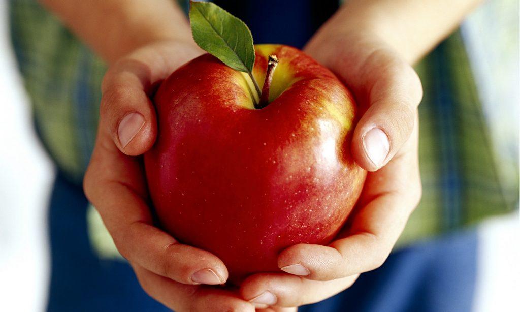 A boy holding an apple.