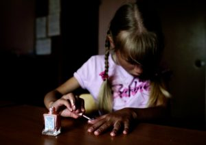 Attempting to paint her nails, the pink polish smears across her finger.