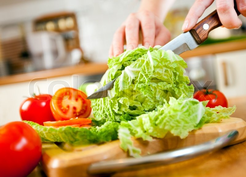 2145201-woman-s-hands-cutting-lettuce-behind-fresh-vegetables