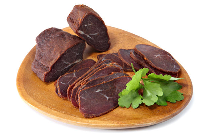 Basturma, dried tenderloin of beef meat, thinly sliced, on a flat wooden dish, Isolated on white background.